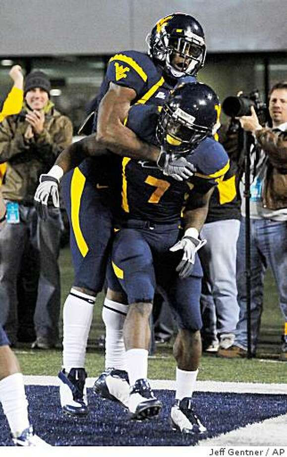 West Virginia's Dorrell Jalloh, top, and Noel Devine celebrate his touchdown against Auburn during the fourth quarter on Thursday, Oct. 23, 2008, in Morgantown, W.Va. Jalloh scored two touchdowns while Devine rushed for a career-high 207 yards and a touchdown. West Virginia won 34-17. Photo: Jeff Gentner, AP