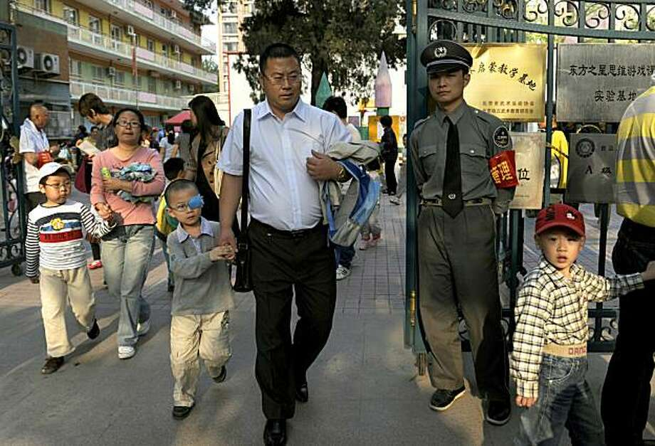 """A security man monitors the situation at the entrance of a kindergarten as parents lead their children out after school in Beijing on May 13, 2010. China's top policeman has vowed to """"severely strike"""" at anyone caught attacking schools, in an angry diatribe following a kindergarten bloodbath -- the fifth such assault in just a few weeks. Photo: Liu Jin, AFP/Getty Images"""