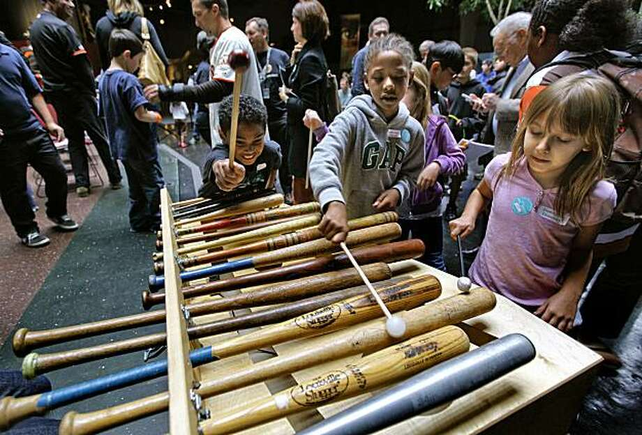 "(left to right) Jason Hilton, Avion Huff and Mackenzie Wallace, of Diablo Vista Elementary school,  play a bat marimba which explores the different sounds the size, shape and material of a bat makes, as the Giants' Mark DeRosa helps to open the ""Science of Baseball"" exhibit at the Exploratorium on Friday May, 14, 2010, in San Francisco, Ca . Photo: Michael Macor, The Chronicle"