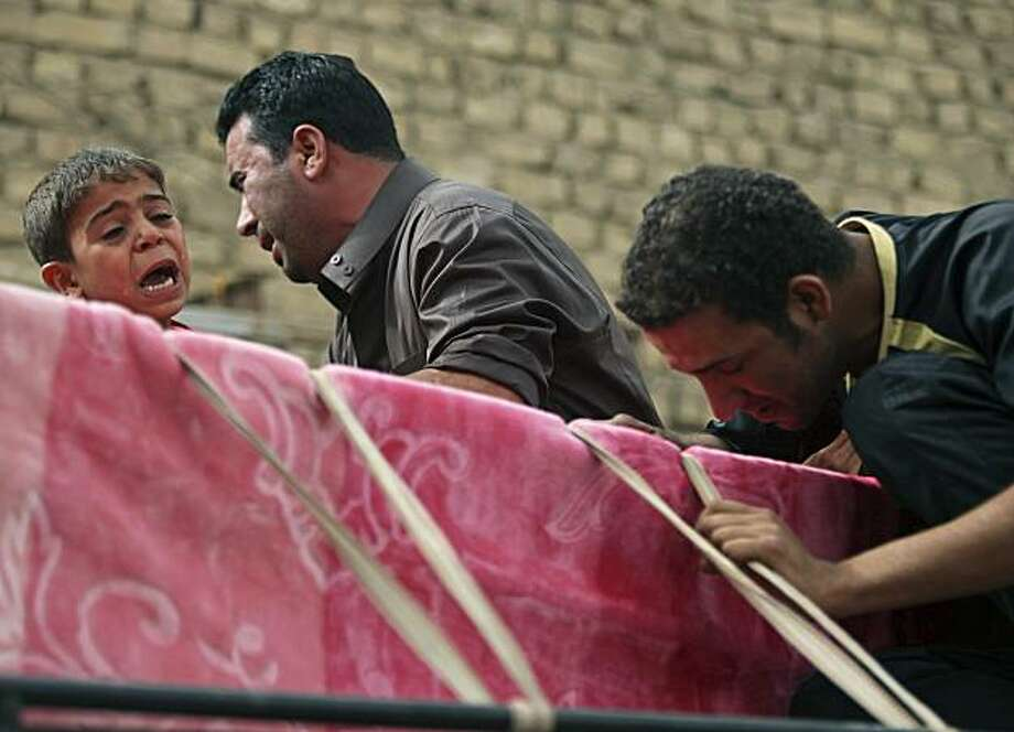 Family members of Rssol Hakim, 18, grieve over his coffin during his funeral in Baghdad, Iraq, Thursday, May 13, 2010. Hakim was killed when a car bomb ripped through a popular cafe on Wednesday evening, killing nine young people. Photo: Karim Kadim, AP