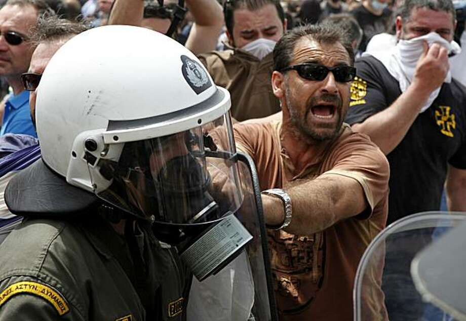 Riot police clash with demonstrators in central Athens, Wednesday, May 5, 2010. Deadly riots over harsh new austerity measures engulfed the streets of Athens on Wednesday, and three people were killed as angry protesters tried to storm parliament, hurledMolotov cocktails at police and torched buildings. Photo: Evi Zoupanou, AP