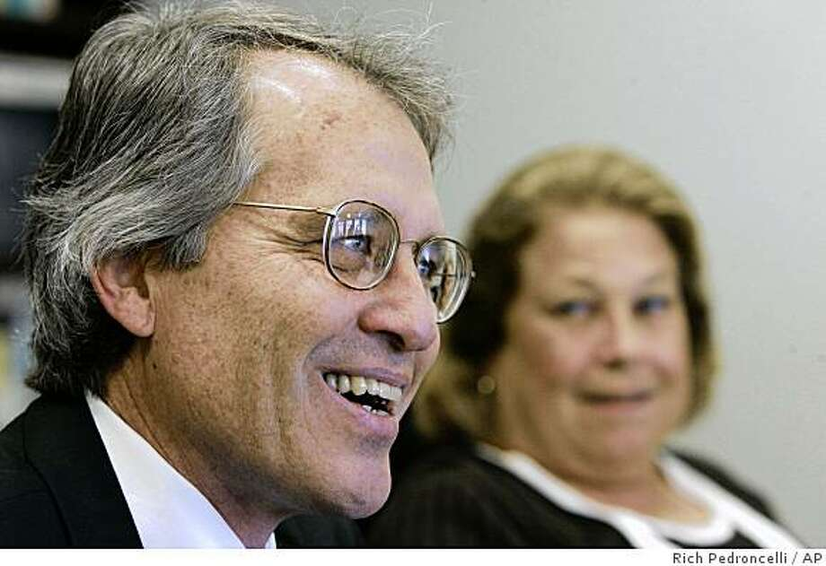 Deputy Legislative Analyst Mac Taylor, left, smiles after he was named as the new legislative analyst at a news conference in Sacramento, Calif., Tuesday, Oct. 21, 2008.  Taylor, 55, will succeed current Legislative Analyst Elizabeth Hill, who is retiring.  At right is Joint Legislative Budget Committee chairwoman Sen. Denise Ducheny, D-San Diego.(AP Photo/Rich Pedroncelli) Photo: Rich Pedroncelli, AP