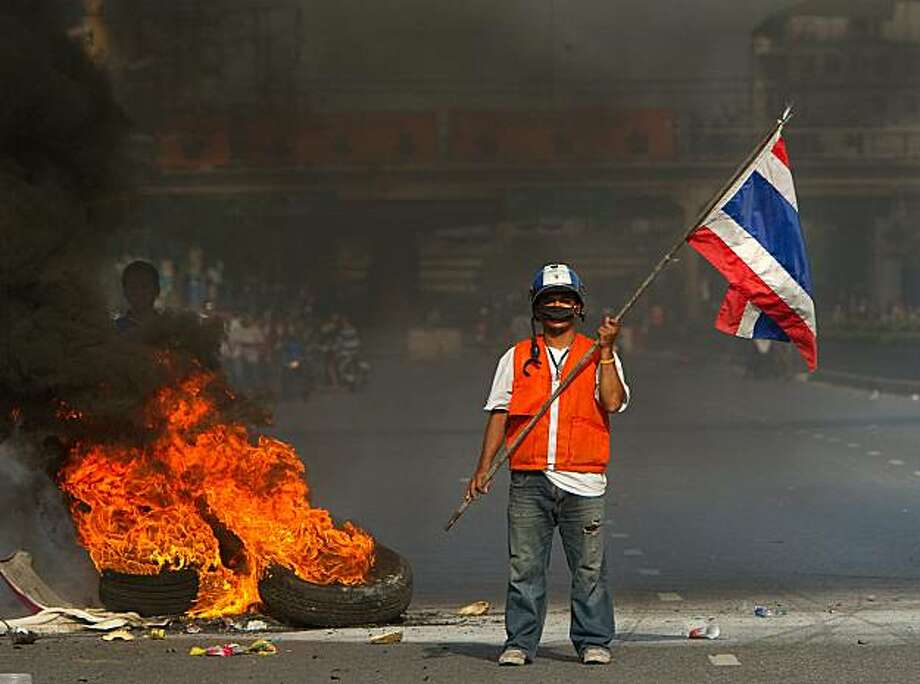 BANGKOK, THAILAND - MAY 14: A red shirt anti-government protester holds a Thai flag as tyres burn in the background during clashes with the military on May 14, 2010 in Bangkok, Thailand. Protesters and military clashed in central Bangkok after the government launched an operation to disperse anti-government protesters who have closed parts of the city for two months. Photo: Paula Bronstein, Getty Images