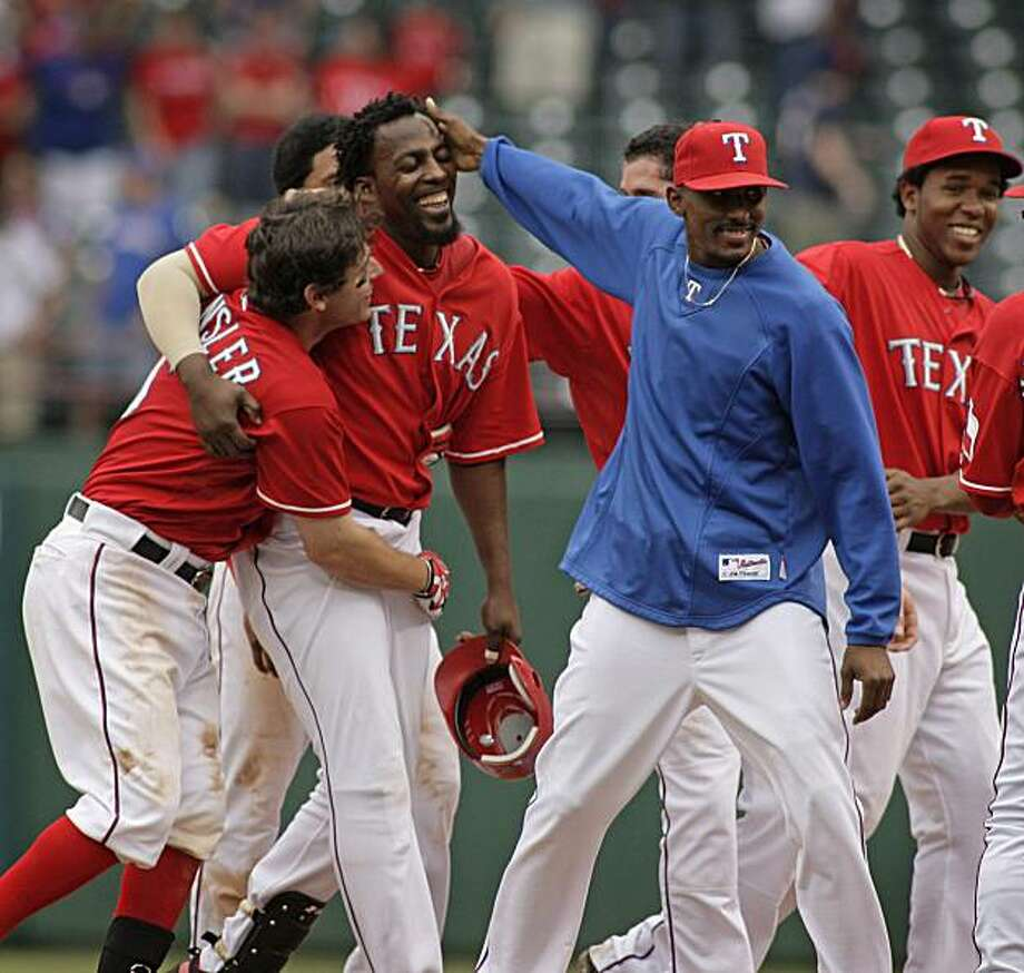 Texas Rangers designated hitter Vladimir Guerrero, middle, is congratulated by teammates after Guerrero's game-winning hit in the 12th inning against the Oakland Athletics at Rangers Ballpark in Arlington, in Arlington, Texas, on Thursday, May 13, 2010. The Rangers beat the A's, 2-1. (Paul Moseley/Fort Worth Star-Telegram/MCT) Photo: Paul Moseley, MCT