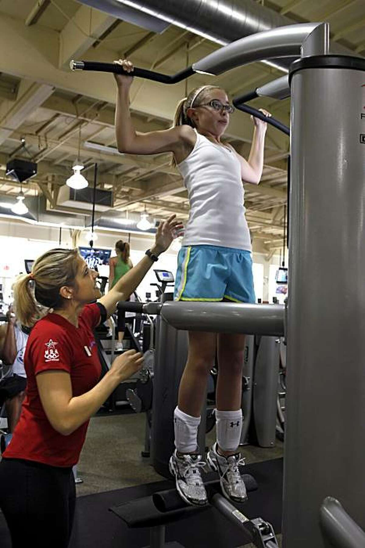 Trainer Terri Whitmore instructs teenager Maddie McPhail in the proper way to lift and do strength training at 24 Hour Fitness in Rheem, Calif., on Tuesday, May 4, 2010. A new study shows that injuries among teen girl weight lifters has shot up 143% between 1990 and 2007.