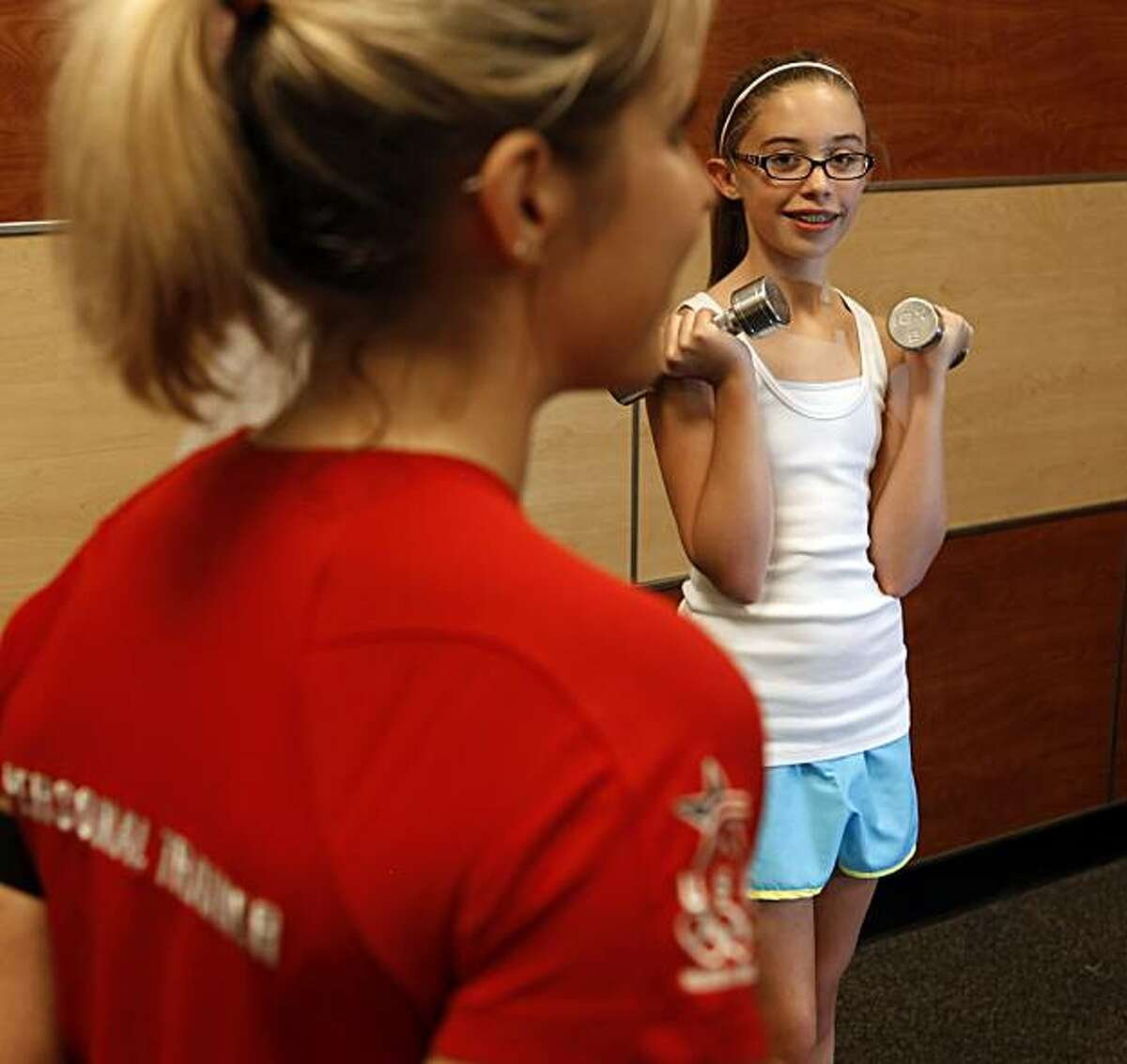 Trainer Terri Whitmore spots teenager Maddie McPhail in the proper way to lift and do strength training at 24 Hour Fitness in Rheem, Calif., on Tuesday, May 4, 2010. A new study shows that injuries among teen girl weight lifters has shot up 143% between 1990 and 2007.