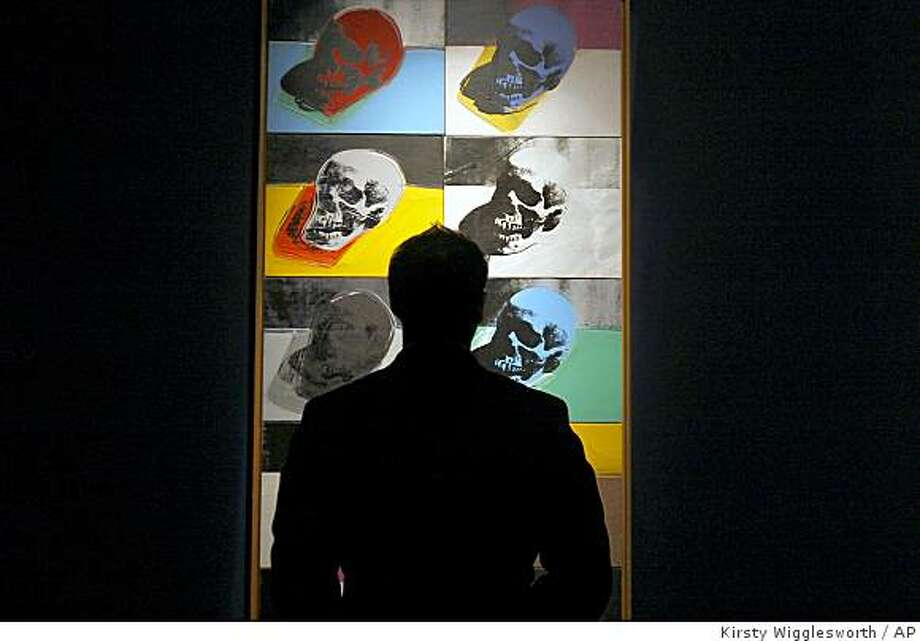 A visitor is silhouetted in front of Andy Warhol's Skulls Series on display at Sotheby's auction rooms in London, Monday, Oct. 13, 2008. The work will be part of Sotheby's Contemporary Art Evening auction on Oct. 17 and is estimated to fetch between GBP 5-7 million (USD 8.6-12 million). (AP Photo/Kirsty Wigglesworth) Photo: Kirsty Wigglesworth, AP
