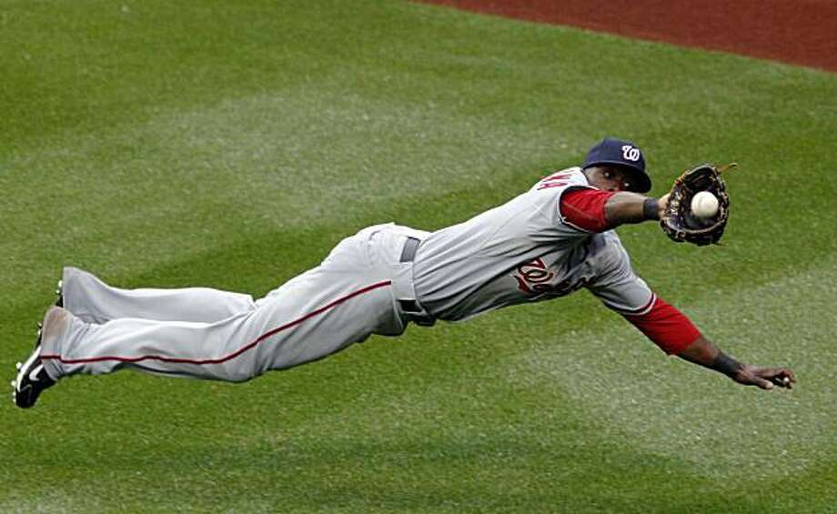 ** CORRECTS NATIONALS PLAYER TO ROGER BERNADINA, INSTEAD OF WILLIE HARRIS ** Washington Nationals' Roger Bernadina makes a diving catch of Jeff Francoeur's fifth inning flyout with bases loaded, for the third out in a baseball game at Citi Field in New York, Wednesday, May 12, 2010. Photo: Kathy Willens, AP