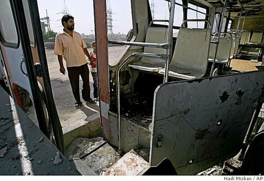 A man inspects a damaged bus after it was hit by a roadside bomb in the al-Mashtal area of eastern Baghdad, Iraq, on Monday, Oct. 20, 2008. The explosion which destroyed two vehicles, killed 2 employees and wounded 7 others including 2 women and the driver, police said. (AP Photo/Hadi Mizban) Photo: Hadi Mizban, AP