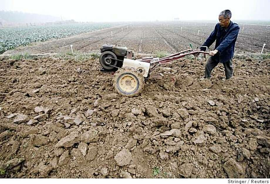 A farmer ploughs farmland on the outskirts of Xiangfan, Hubei province October 8, 2008. China will further expand its reforms to the rural financial sector next year to give businesses in the countryside greater access to credit and to increase rural incomes, the banking regulator said on Wednesday. Picture taken October 8, 2008. REUTERS/Stringer (CHINA).  CHINA OUT. NO COMMERCIAL OR EDITORIAL SALES IN CHINA. Photo: Stringer, Reuters