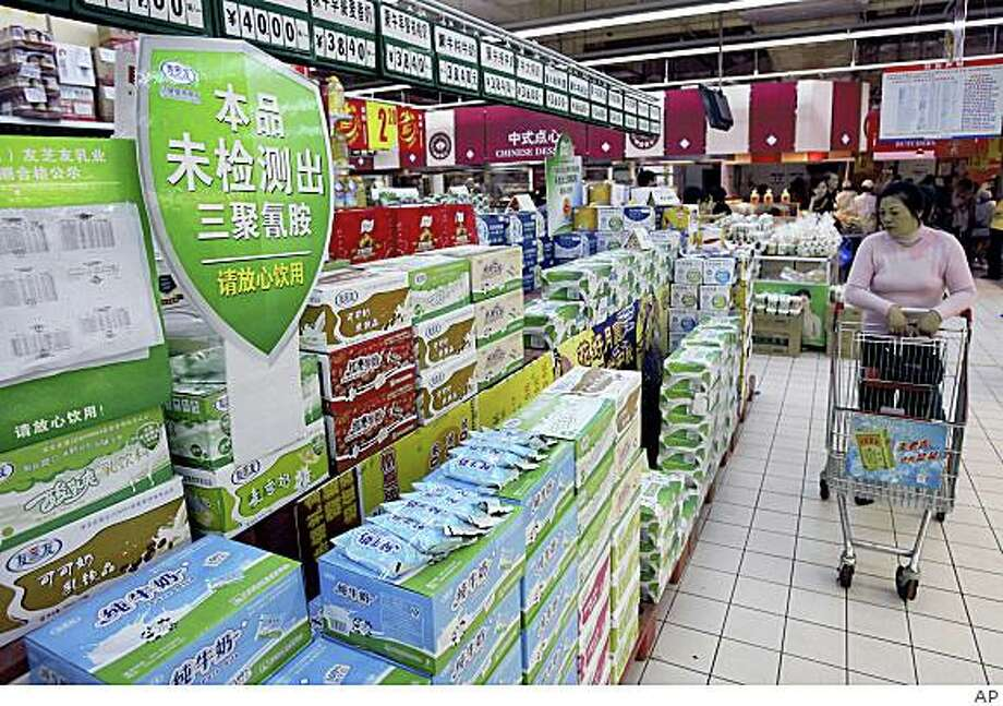 "A woman looks at the milk products with a notice board reading ""Free of Melamine, feel safe to take"" on display at a supermarket in Wuhan in central China's Hubei province, on Oct. 9, 2008. Photo: AP"