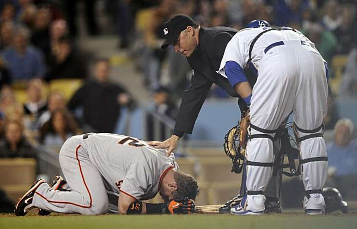 San Francisco Giants' Aaron Rowand lays on the ground as Los Angeles Dodgers catcher Russell Martin, right, and home plate umpire Dan Iassogna look over him after getting hit in the head with a pitch during the fith inning of their Major League Baseball game, Friday, April 16, 2010, in Los Angeles.