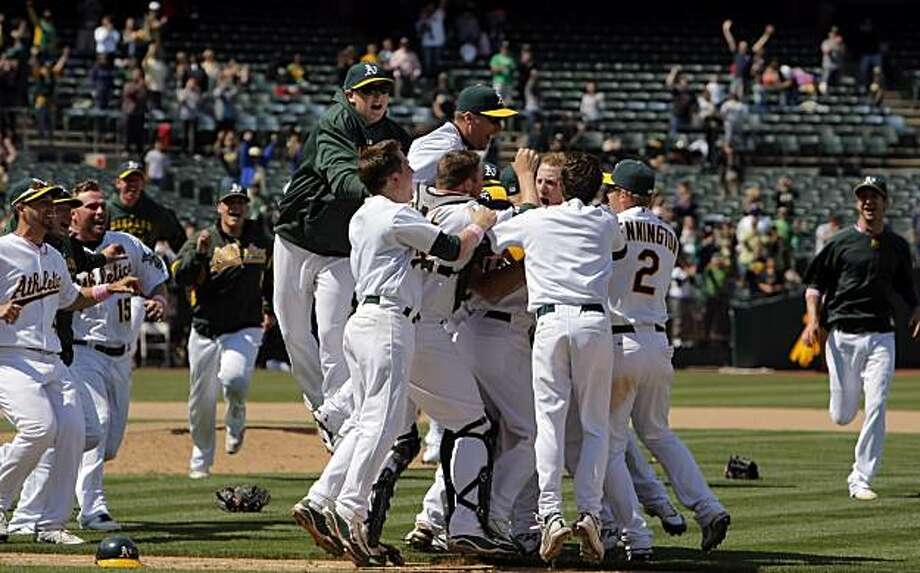 The Athletics mob pitcher Dallas Braden after his perfect game against the Tampa Bay Rays in Oakland on Sunday. Photo: Carlos Avila Gonzalez, The Chronicle