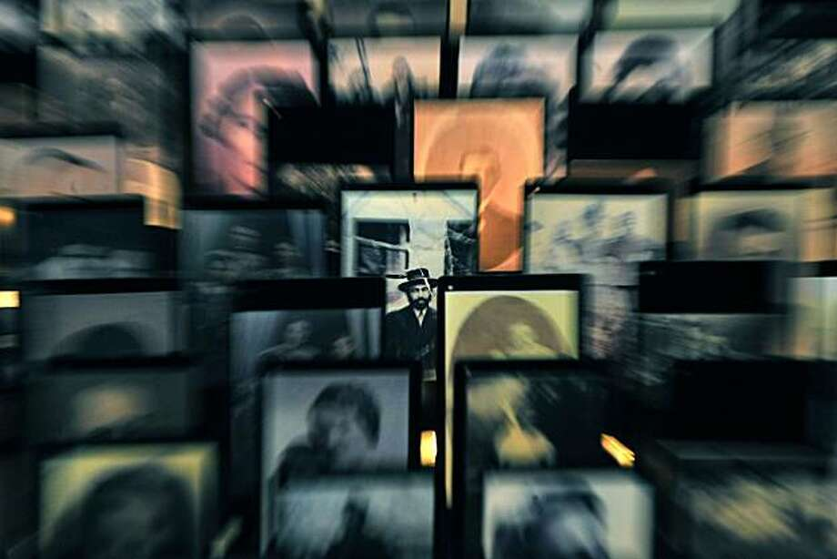 A picture of a man is seen among candle-lit photos of the victims exhibited in the Holocaust Memorial Centre on the Holocaust Memorial Day in Budapest, Hungary, Friday, April 16, 2010, the 66th anniversary of the beginning of the Hungarian holocaust during which some 600 thousand Jewish Hungarians were deported to Nazi death camps. Photo: Tamas Kovacs, AP