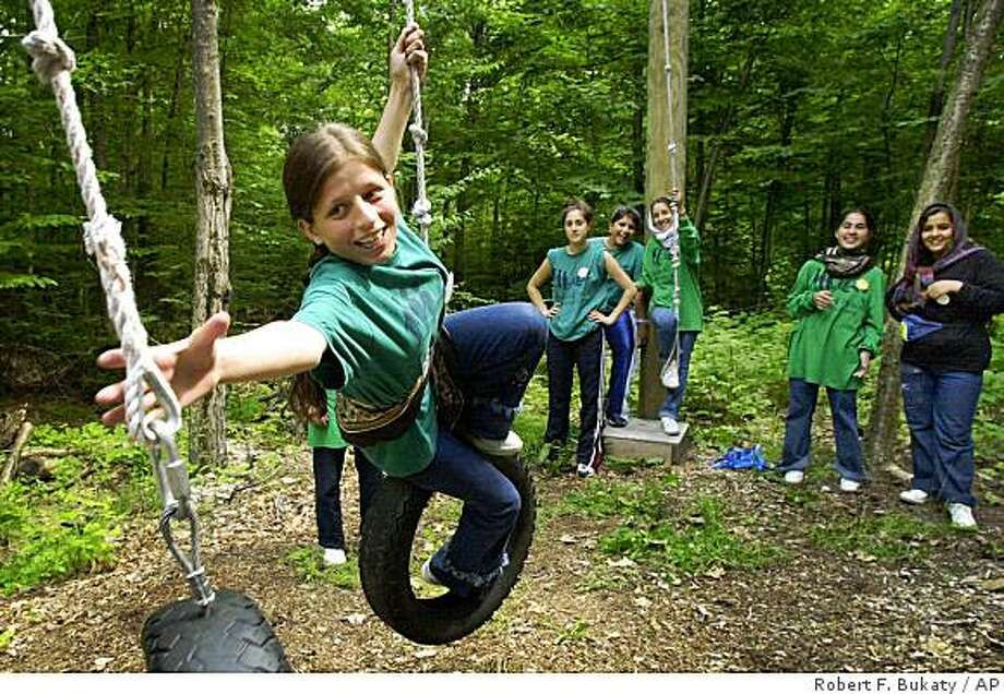 Abida Ayda, 14, of Afghanistan, reaches for a rope swing during a trust-building exercise at the Seeds of Peace Camp, in this June 30, 2002 file photo, in Otisfield, Maine. Since 1993, Seeds has brought together about 2,000 youths from warring lands - Israelis and Palestinians, Indians and Pakistanis, Cypriot Turks and Greeks, Bosnian Muslims and Serbs and tribal members from Afghanistan. Photo: Robert F. Bukaty, AP