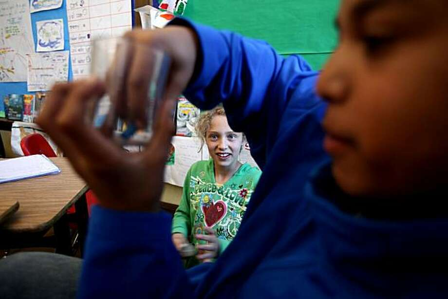 Alvarado Elementary School students Dana Suleiman (center) watches fellow classmate Nicolas James conduct a science experiment during UCSF Professor Bruce Alberts' hands-on lessons related to air pressure, which he does through UCSF's Science & Health Education Partnership on Friday, April 30, 2010 in San Francisco, Calif. Photo: Jessica Pons, The Chronicle