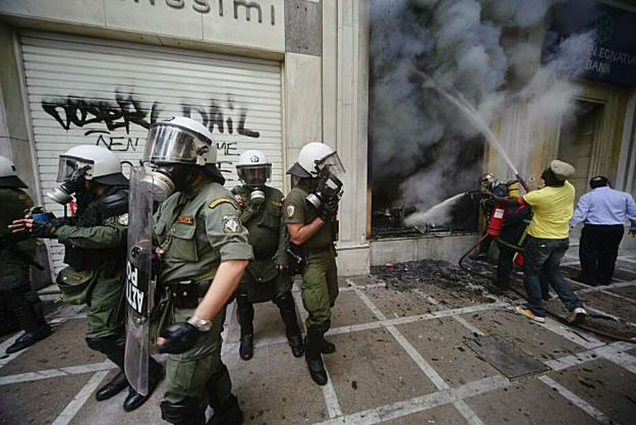 Riot police stands next to a burning Marfin Egnatia Bank, where three people died, in central Athens, Wednesday, May 5, 2010. Greek fire officials say three people died in a blaze that broke out at an Athens bank during rioting over government austerity measures. An estimated 100,000 people took to the streets Wednesday during a nationwide wave of strikes against spending cuts aimed at saving the country from bankruptcy Photo: Iakovos Hatzistavrou, AP