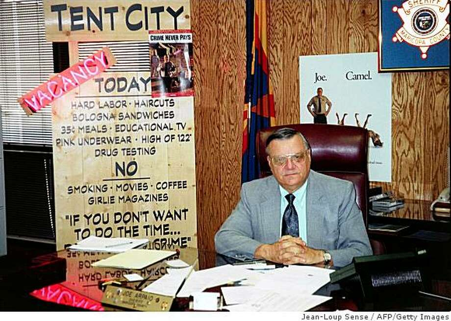 "PHOENIX, AZ - MAY 28:  Maricopa County Sheriff Joe Arpaio who claims to be ""the toughest sheriff in the United States"" sits behind his desk next to a sign for the Tent City prison camp with a vacancy sign 21 May.  Among the rules at the tent city prison that houses 1000 prisoners are hard labor, haircuts, bologna sandwiches, pink underwear and no girlie magazines, smoking or coffee.  (Photo credit should read JEAN-LOUP SENSE/AFP/Getty Images) Photo: Jean-Loup Sense, AFP/Getty Images"