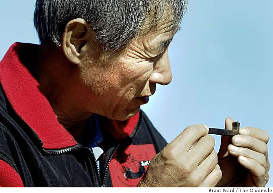 Skipper Liu Ning Sheng examines an authentic nail used in the construction of the ancient junk fleet. Photo: Brant Ward, The Chronicle