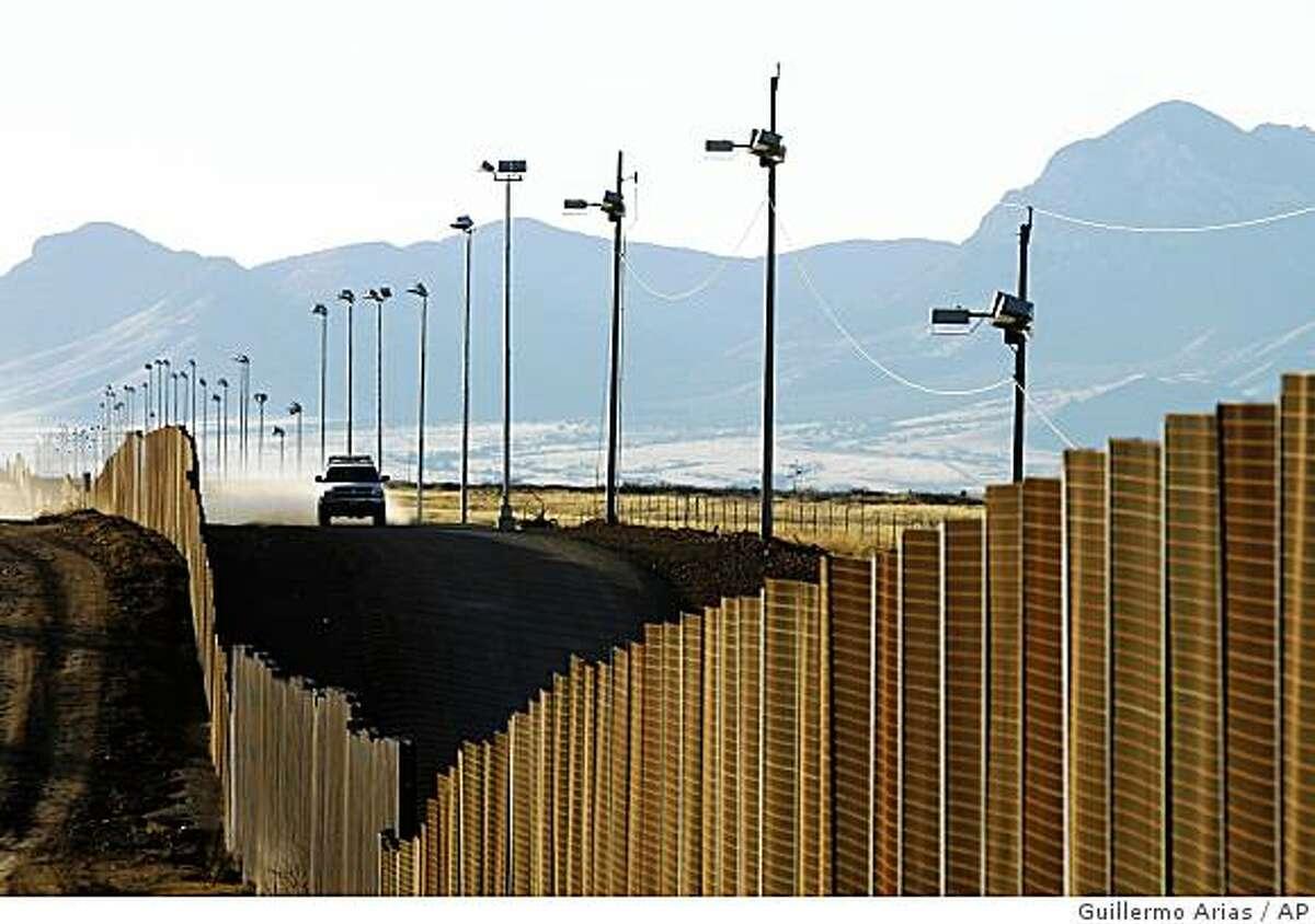 A U.S border patrol vehicle rides along the fence at the U.S-Mexican border near Naco, Mexico, Sunday, Jan. 13, 2008. (AP Photo/Guillermo Arias)