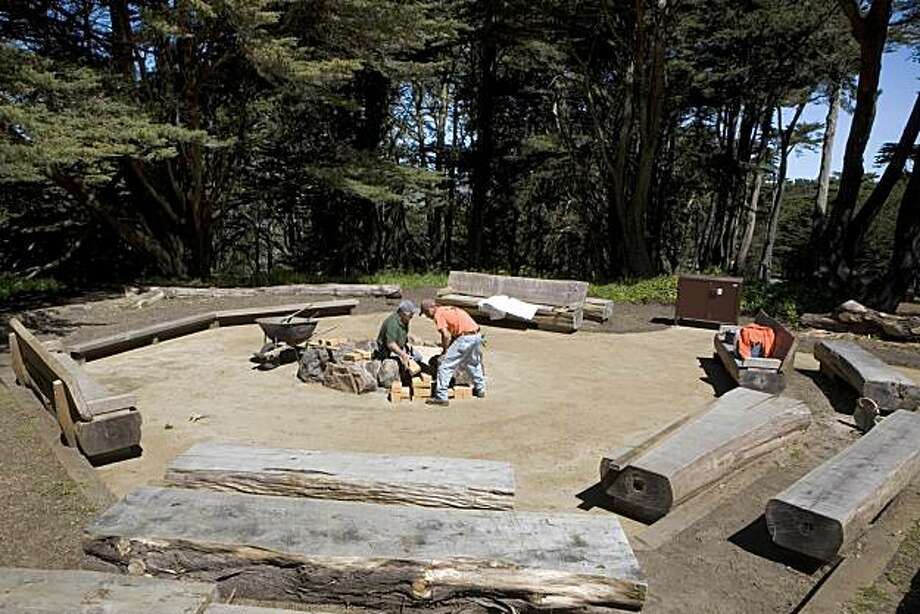 Rodolfo Vargas and Cristobal Carranza with Bauman Landscape & Construction put the finishing touches on the fire circle at Rob Hill Campground in the Presidio in San Francisco on Friday, April 30, 2010.   Rob Hill Campground, the only (legal) campground in the city in the Presidio, off Washington Boulevard is reopening Saturday after a 20-month renovation. Kat Wade / Special to the Chronicle Photo: Kat Wade, Special To The Chronicle