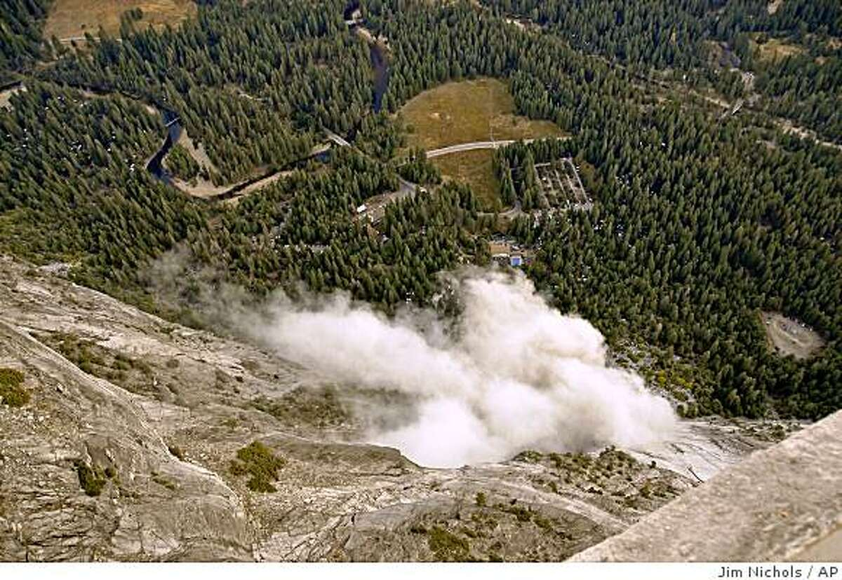 A dust cloud is seen from the Glacier Point overlook during a rock fall that damaged lodging facilities in Curry Village in Yosemite National Park, Wed., Oct. 8, 2008. (AP Photo/Jim Nichols)