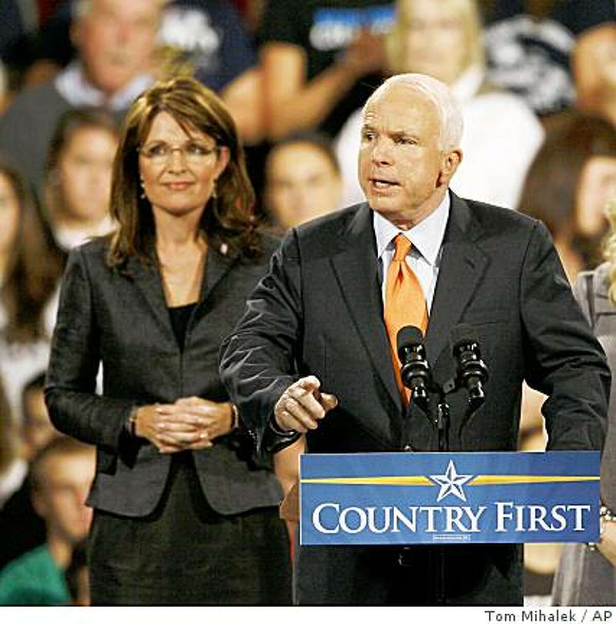 Republican presidential candidate, Sen. John McCain, R-Ariz., speaks as Republican vice-presidential candidate, Alaska Gov. Sarah Palin, left, looks on during a rally held at Lehigh University in Bethlehem, Pa, Wednesday, Oct. 8, 2008. McCain spoke about fixing the economy, funding defense and health care. (AP Photo/Tom Mihalek)