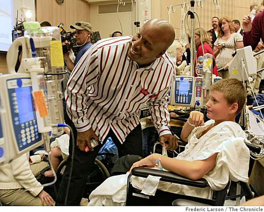 Barry Bonds poses for a photograph with patient Travis Hopkins (right) at UCSF Hospital in San Francisco, Calif., to promote the upcoming Macy's Christmas tree lighting on October 7, 2008. Photo: Frederic Larson, The Chronicle