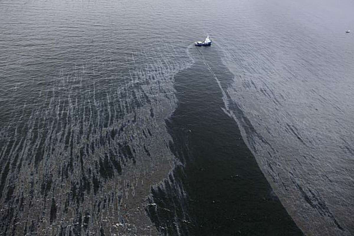 In this aerial photo taken in the Gulf of Mexico more than 50 miles southeast of Venice on Louisiana's tip, a boat with an oil boom tries to contain oil spilled from the explosion and collapse of the Deepwater Horizon oil rig, approximately seven miles from where the rig sunk, on Friday, April 23, 2010.