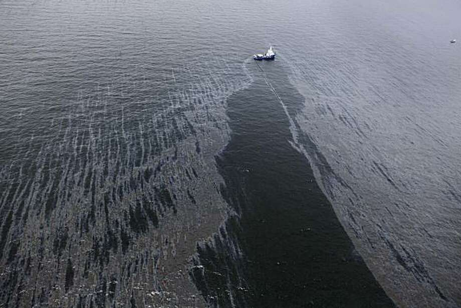 In this aerial photo taken in the Gulf of Mexico more than 50 miles southeast of Venice on Louisiana's tip, a boat with an oil boom tries to contain oil spilled from the explosion and collapse of the Deepwater Horizon oil rig, approximately seven miles from where the rig sunk, on Friday, April 23, 2010. Photo: Gerald Herbert, AP