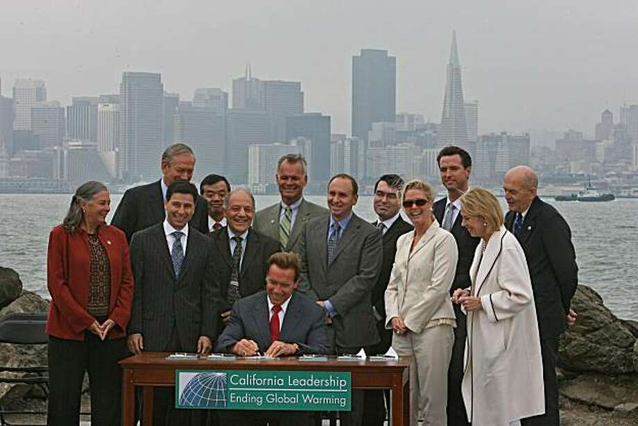 California became the first state to impose total caps on greenhouse gasses when Governor Arnold Schwarzenegger signed a sweeping global warming bill with other officials. The governor was joined in person by Democratic lawmakers and San Francisco Mayor Gavin Newsom during the signing ceremony on Treasure Island Wednesday morning. British Prime Minister Tony Blair also addressed the crowd through a satellite video hook-up, congratulating the governor and the legislature for passing such bold legislation. The law that resulted from a bi-partisan effort imposes a first-in-the-nation emissions cap on utilities, refineries and manufacturing plants in a bid to curb the gases scientists blame for warming the Earth. California's efforts on global warming have gained international attention since Schwarzenegger and the state's legislative Democrats reached an accord last month. The law hands the Republican governor a key victory in an election year where he has sought to portray himself as a friend to the environment. Photo: Frederic Larson, The Chronicle