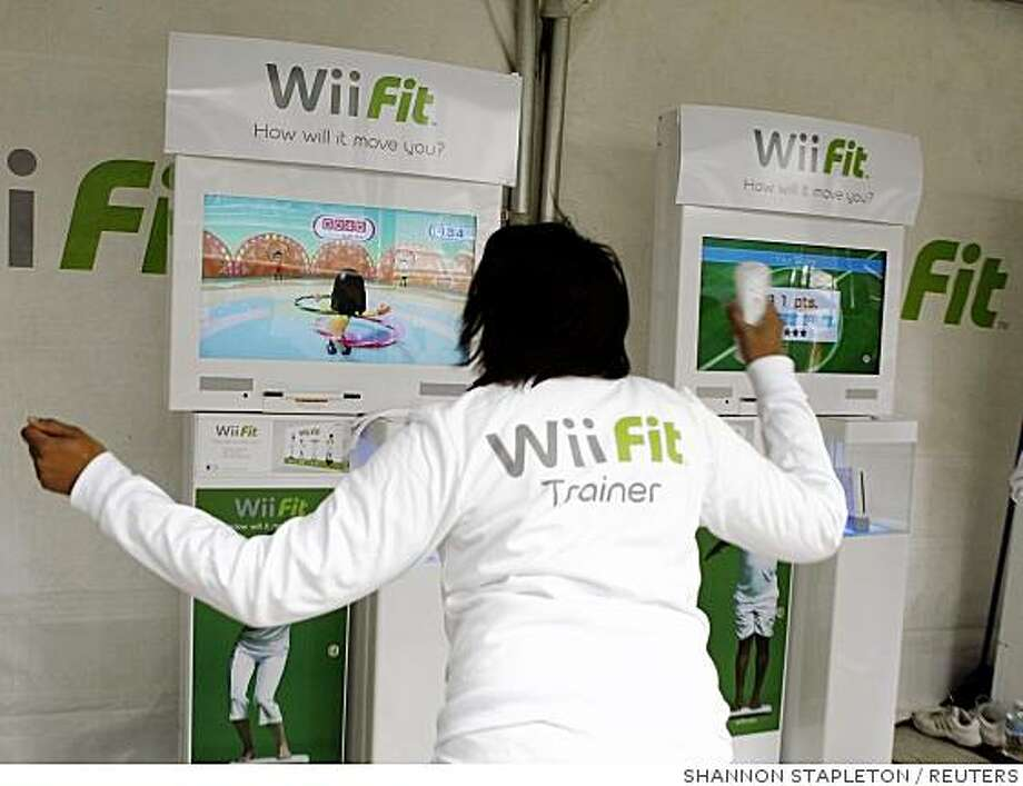 """A woman demonstrates an interactive hula hoop game on Nintendo's Wii Fit, a new interactive fitness game for the Wii system, during the product launch in New York in this file image from May 19, 2008. Girls and young women are a """"pot of gold"""" for video game makers, said George VanHorn, senior analyst at  market research firm IBISWorld. Picture taken May 19.     To match feature VIDEOGAMES/GIRLS    REUTERS/Shannon Stapleton (UNITED STATES) Photo: SHANNON STAPLETON, REUTERS"""