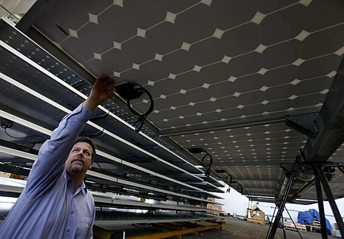 Tom Starrs inspects the underbelly of a solar panel at the SunPower facility in Richmond, Calif., on Thursday, March 18, 2010. SunPower recently announced a deal with Southern California Edison to provide solar technology that will produce up to 200 megawatts of energy.
