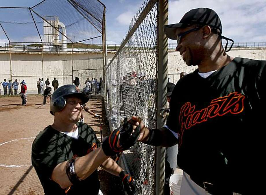 Inmate player Redd Casey (left) is congratulated by a teammate after driving in a run in the first game of the season for the San Quentin Giants in San Quentin on Saturday. Photo: Paul Chinn, The Chronicle