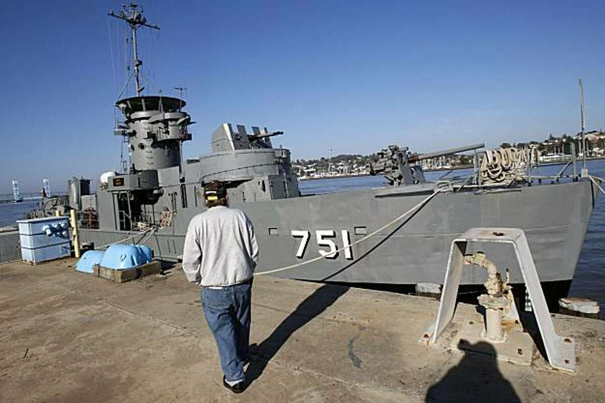 Larry Collins from Vallejo walks the dock after concluding a long day helping restore the ship. A pair of twin 40 caliper guns looks down over a 3 inch 50 signal gun on the bow. Bill Mason and his volunteer group plan to open the only remaining vessel of 130 built during WW11. Mason and others served aboard a Mighty Midget gunboat called an LCS in World War II and never forgot it. He and his shipmates brought back the last of these small warships from Thailand were it was loaned out to the Thai Navy.