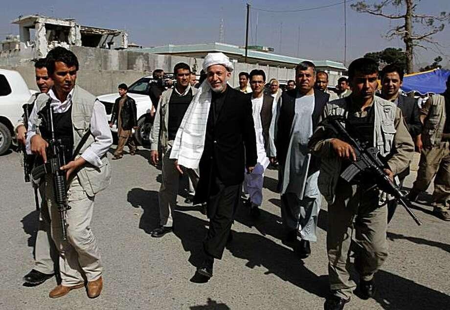 Afghan President Hamid Karzai, center, surrounded by his body guards walks through Kandahar city, south of Kabul, Afghanistan, Monday, April 5, 2010. Photo: Allauddin Khan, AP