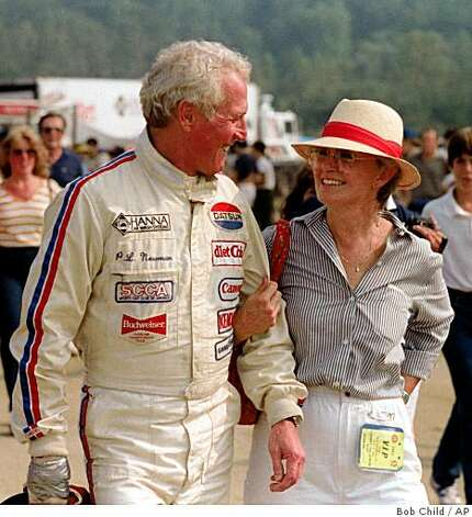 In this Sept. 6, 1983 file photo, Paul Newman and his wife, Joanne Woodward, smile as they walk through the paddock area at Lime Rock Park race track in Lime Rock, Conn. Spokeswoman for Paul Newman says, Saturday, Sept. 27, 2008, that the screen legend has died at age 83 after battling cancer. Photo: Bob Child, AP
