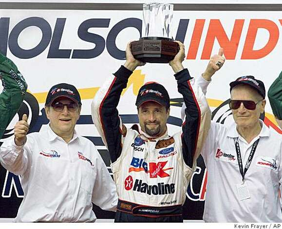 Newman/Haas Racing's Michael Andretti, center, raises the trophy as he celebrates with team owners Carl Haas, left, and actor Paul Newman on the podium after winning the Molson Indy in Toronto Sunday July 16, 2000. It was Andretti's sixth career win in Toronto. Photo: Kevin Frayer, AP