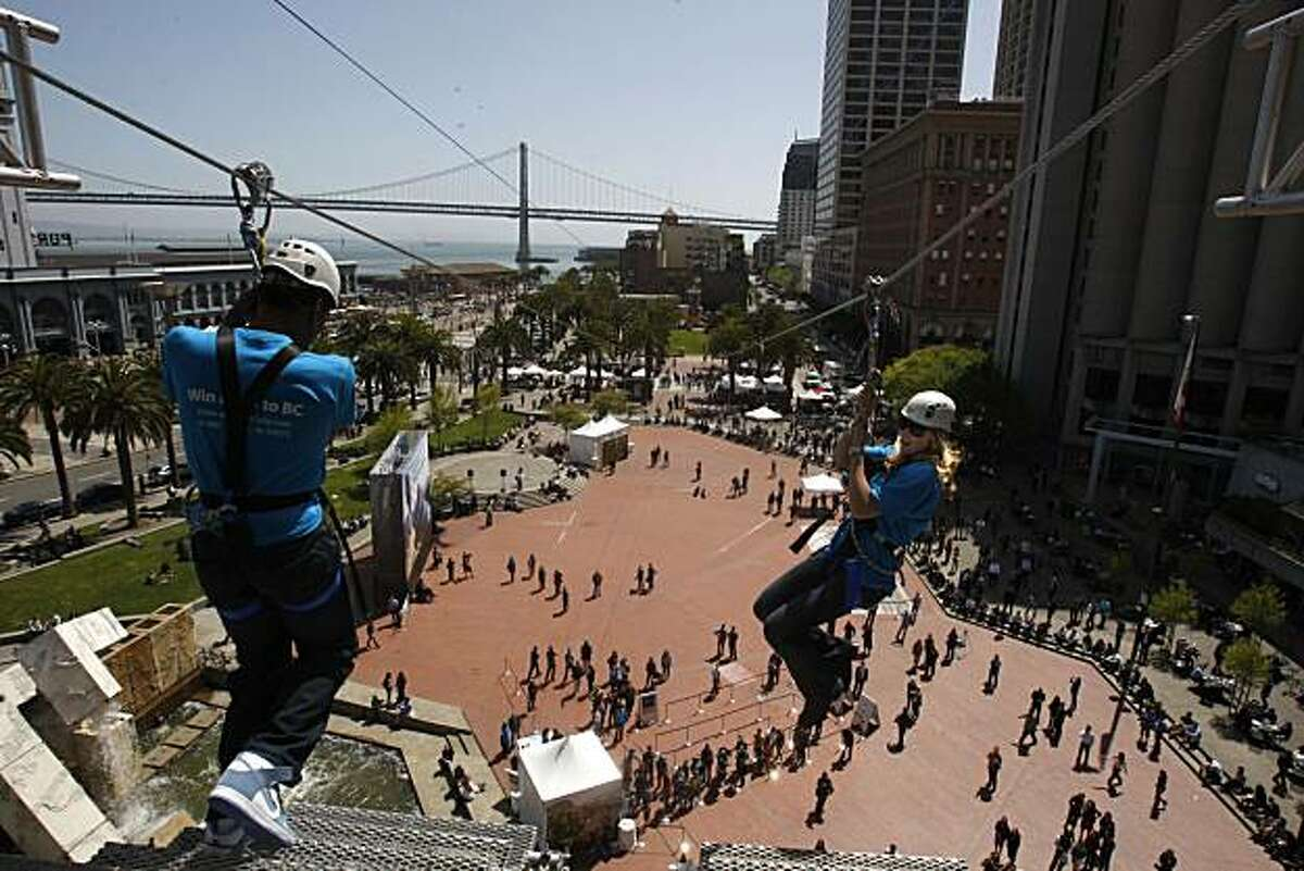 2010 gold medalists american speed skater Shani Davis (left) takes a leap as Canadian ski cross racer Ashleigh McIvor (right) watches on the zipline at Justin Herman Plaza in San Francisco, Calif., on Thursday, April 8, 2010. They launch an 11 day event called