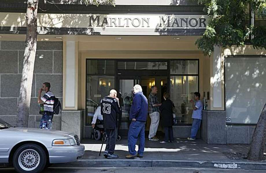 People gather outside the Marlton Manor public housing complex in San Francisco is photographed on Wednesday, April 7, 2010 where the FBI arrested resident Gregory Lee Giusti, 48, for allegedly making threatening and harassing phone calls to House SpeakerNancy Pelosi regarding health care reform. Photo: Eric Risberg, AP