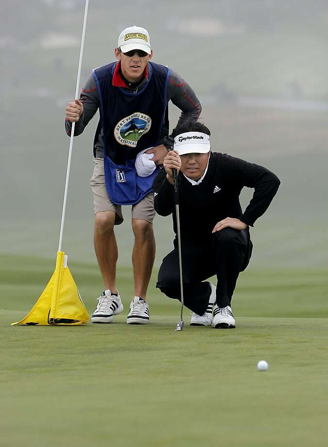 Charlie Wi, the tournament leader lines up his eagle putt with the help from his caddie Mark Urbanek, on the 6th hole at Pebble Beach, he made a birdie, during second round action at the 2012 AT&T Pebble Beach National Pro-Am Golf Tournament, in Pebble Beach, Ca. on Friday Feb. 10, 2012. Photo: Michael Macor, SFC