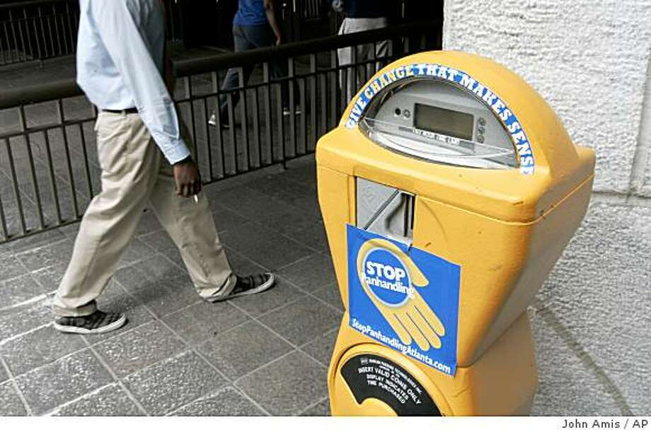 **APN ADVANCE FOR SUNDAY SEPT. 28**  A pedestrian walks pst one of the city of Atlanta's donation collection meters set up in various downtown locations to hopefully help reduce panhandling by providing an alternative way to give, Friday Sept. 12, 2008, in Atlanta. (AP Photo/John Amis) Photo: John Amis, AP