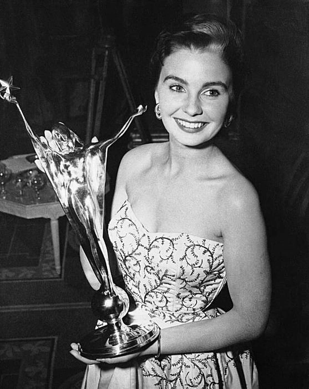 """In this May, 24, 1950 file photo, Jean Simmons, British screen actress, holds the trophy she receives in London after being voted her country's No. 1 film actress of the year in the fifth National Film Award ballot. Simmons, the stunning beauty who sang with Marlon Brando in """"Guys and Dolls"""" and played Ophelia to Laurence Olivier's Hamlet died Friday, Jan. 22, 2010. She was 80."""