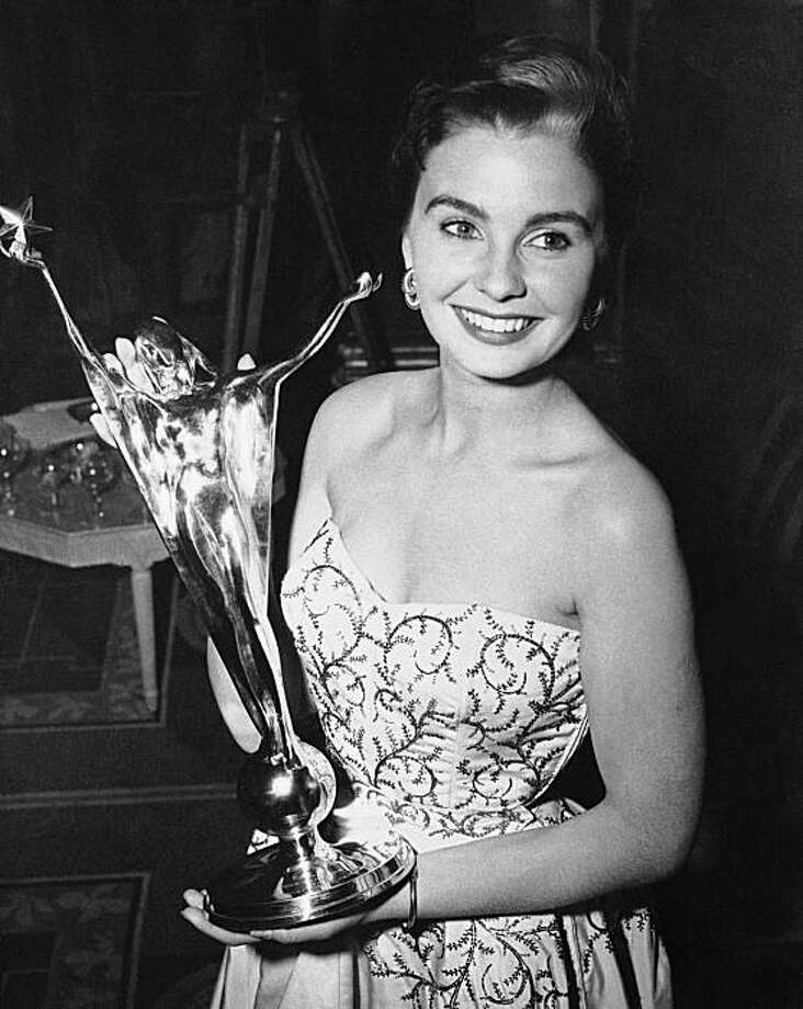 "In this May, 24, 1950 file photo, Jean Simmons, British screen actress, holds the trophy she receives in London after being voted her country's No. 1 film actress of the year in the fifth National Film Award ballot. Simmons, the stunning beauty who sang with Marlon Brando in ""Guys and Dolls"" and played Ophelia to Laurence Olivier's Hamlet died Friday, Jan. 22, 2010. She was 80. Photo: AP"