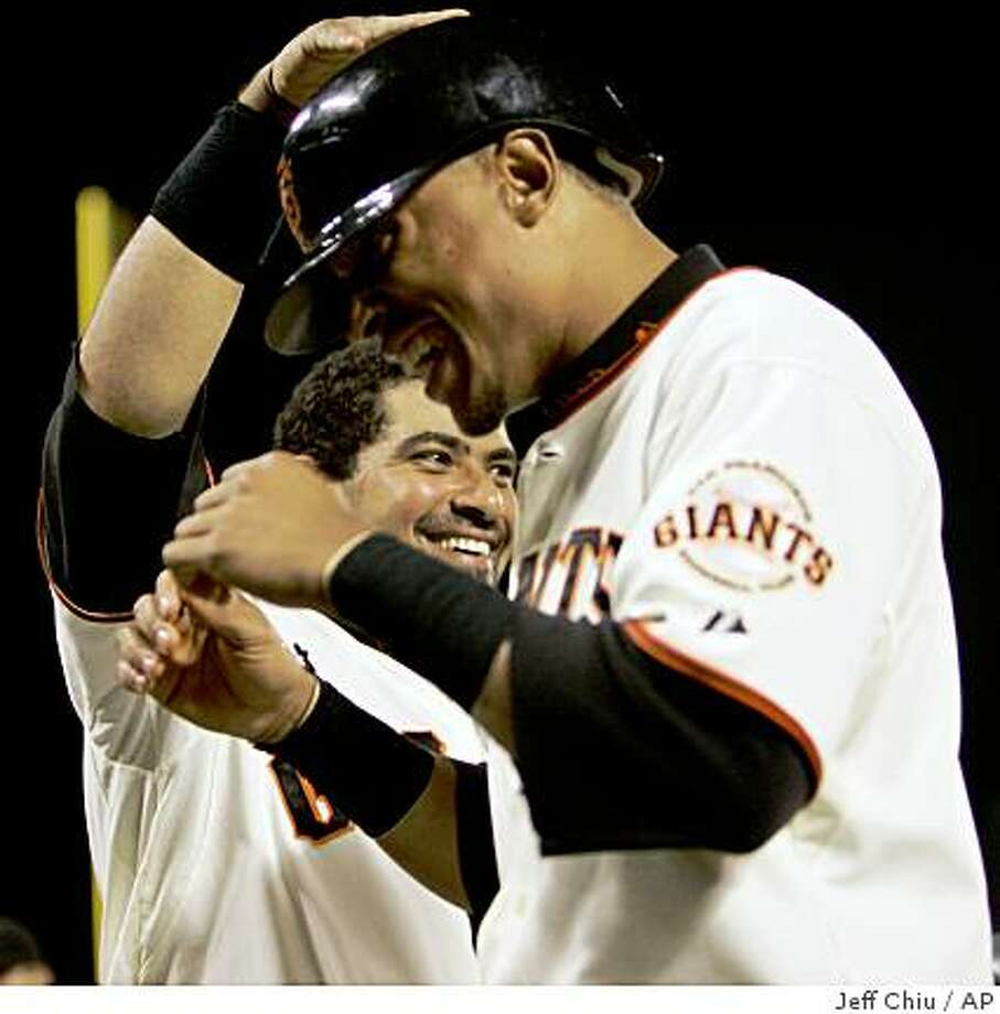 San Francisco Giants' Bengie Molina, celebrates with Emmanuel Burriss, after Molina's two-run home run against the Los Angeles Dodgers in the sixth inning of a baseball game in San Francisco, Friday, Sept. 26, 2008. The umpires for the Dodgers-Giants game Friday night went to instant replay to determine that Molina's hit to right-field was a home run rather than a single as they initially ruled. (AP Photo/Jeff Chiu) Photo: Jeff Chiu, AP