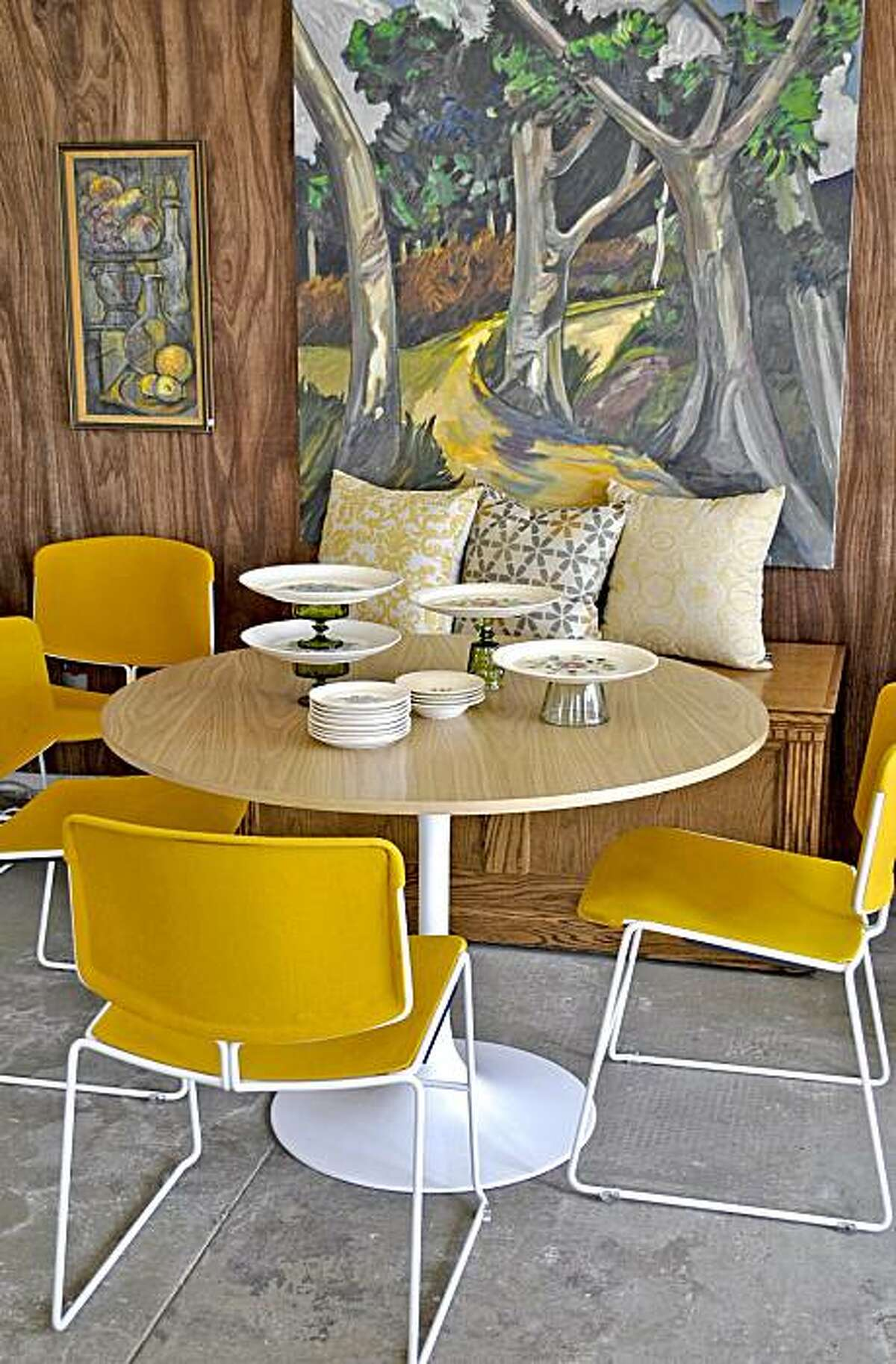 Yellow chairs surround a refurbished tulip table at Lot 49 in Oakland