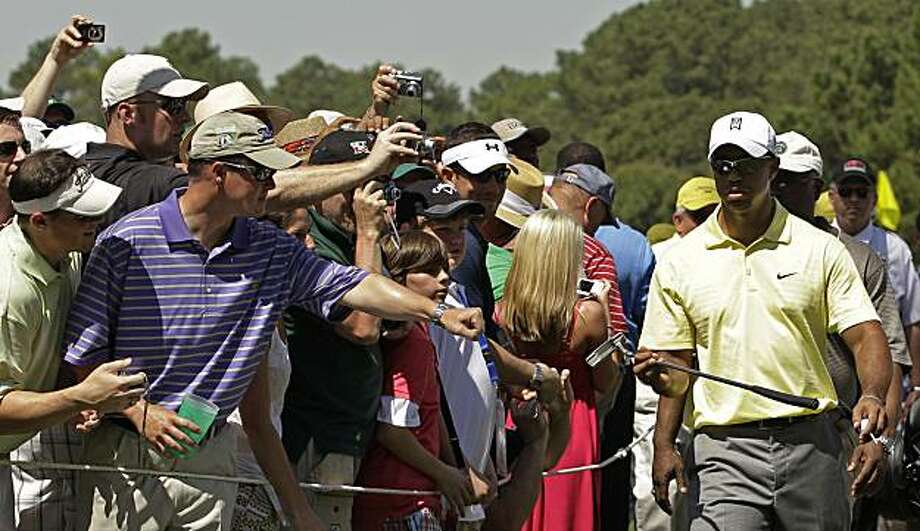 Spectators reach out to greet Tiger Woods as he walks up the 18th green during a practice round at the Masters golf tournament in Augusta, Ga., Tuesday, April 6, 2010. The tournament begins Thursday, April, 8. Photo: Charlie Riedel, AP