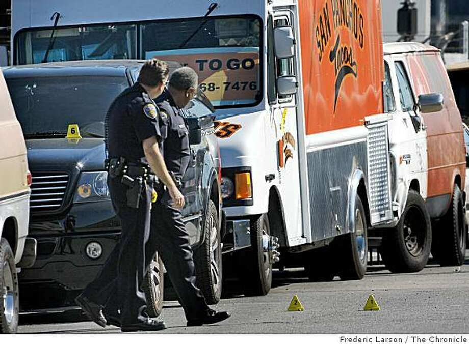 San Francisco Police officers walk by the scene of a shooting that resulted in the death of a man in the industrial section of Portrero Hill. Photo: Frederic Larson, The Chronicle