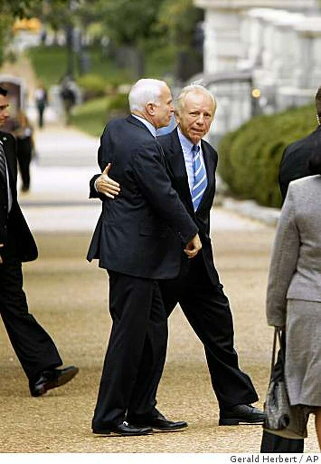 Republican presidential candidate, Sen. John McCain, R-Ariz., is greeted by Sen. Joe Lieberman, I-Conn., right, as he arrives at the Russell Senate Office Building on Capitol Hill in Washington, Thursday, Sept. 25, 2008. McCain will be meeting at the White House with President Bush, other leading lawmakers and presidential nominee Barack Obama later in the day on the financial crisis. (AP Photo/Gerald Herbert) Photo: Gerald Herbert, AP