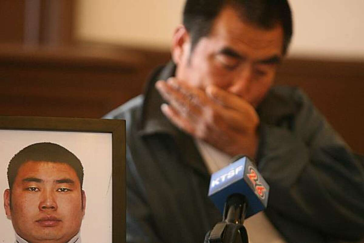 Huiquan Chang, 48, El Cerrito, weeps as he speaks about his son Jinzhou Chang(in the photo beside him), who was murdered as they were both working at an apartment building on Belmont St. in El Cerrito.